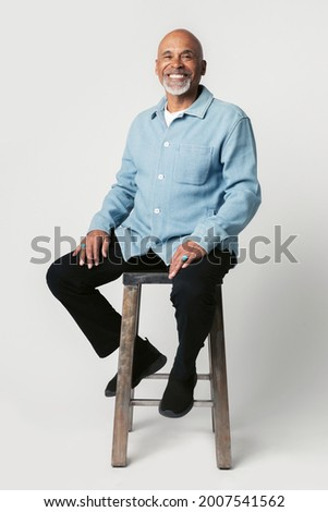 Happy retired man sitting on a stool