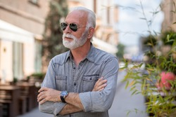 Happy rich old man with beard and sun glasses on street posing and smiling, portrait, blurred city street background