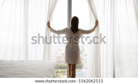 Photo of Happy rich young woman wear night robe stand at big window open lace curtains in bedroom look outside enjoy view dream feel motivated in modern home hotel, good morning lifestyle concept, rear view