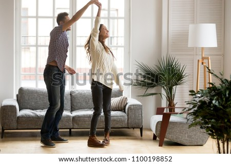 Happy romantic couple having fun in new home, man holding womans hand up leading in dance enjoying weekend, cheerful young family feeling excited spending time together in cozy modern living room