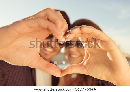 Happy romantic couple in love gesturing a heart with fingers #367776344