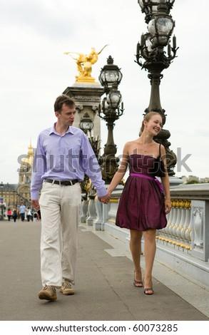 Happy romantic couple in Paris, walking crossing the Pont Alexandre III