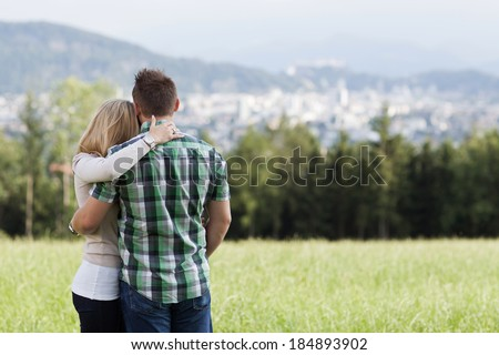 Happy romantic couple standing arm in arm with their backs to the camera in a field looking out over the countryside to a distant town
