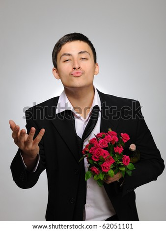 Happy romantic husband holding rose flower and vine bottle prepared to celebrate. gray background