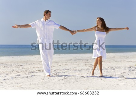 Happy romantic man and woman couple dancing and holding hands on a deserted tropical beach with bright clear blue sky