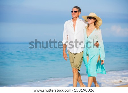 Happy Romantic Middle Aged Couple Enjoying Walk on the Beach, Vacation Retirement Concept
