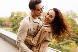 Happy romantic moments of lovely couple dancing and fooling around in park during dating.