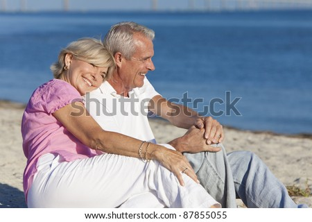 Happy romantic senior man and woman couple together on a deserted beach