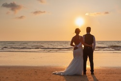 happy romantic wedding couple in love and look at the horizon with sunset
