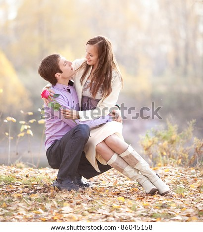 happy romantic young couple spending time outdoor in the autumn park