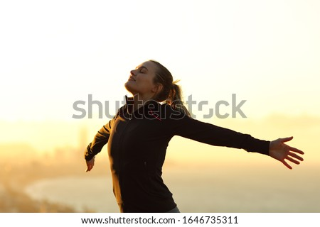 Happy runner breathing fresh air outstretching arms at sunset in the city outskirts Photo stock ©