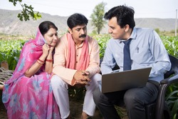 Happy rural indian farmer family with agronomist or banker use laptop. Man officer showing policy on computer screen, Financial support or farming crop loan,  husband wife with government scheme agent