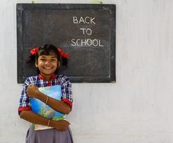Happy Rural School Girl wearing School Uniform Standing in Front of A Black Board Written