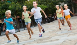 happy russian kids actively playing and running together on street on summer day