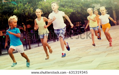 happy russian kids actively playing and running together on street on summer day #631319345
