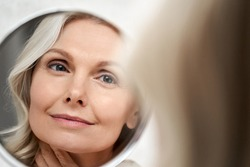 Happy 50s middle aged woman model touching face skin looking in mirror reflection. Smiling mature old lady pampering, healthy moisturized skin care, aging beauty, skincare treatment cosmetics concept.