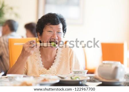 Happy 60s Senior Asian Woman eating vegetable at restaurant