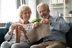 Happy 60s spouses knitting seated on couch, spend free time do favourite hobby, holding needles knitting together, wife helps to husband, family enjoy common activity, retired well-being life concept