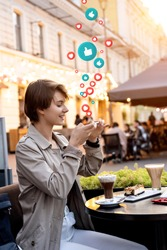 Happy 20s teen girl blogger hold phone take mobile food photo sit at city cafe table get many likes hearts. Young vlogger influencer shoot Instagram stories social media vertical video on smartphone.