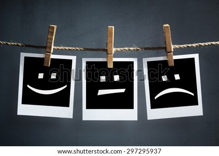 Happy, sad and neutral emoticons on instant print transfer photographs hanging on a clothesline #297295937
