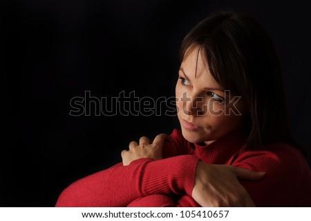 Happy sad Caucasian female sitting on a dark background