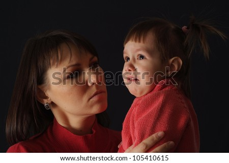 Happy sad Caucasian mama with a daughter on a dark background