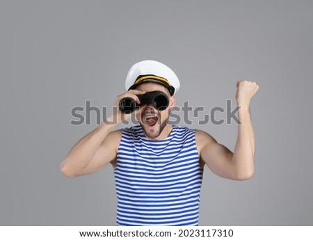 Happy sailor looking through binoculars on grey background Foto stock ©