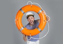 Happy sailor with orange ring buoy on grey background