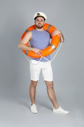 Happy sailor with ring buoy on light grey background