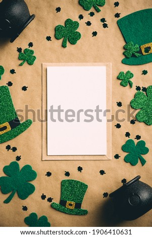 Happy Saint Patrick's day concept. Vertical banner design with greeting card mockup, Irish elf hats, pots of gold, shamrock clover leaves on kraft paper background. Vintage, retro style Foto d'archivio ©