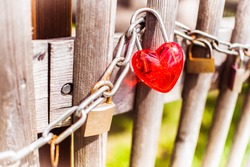 Happy Saint Valentines day card background. Lovely new heart shaped bright red and other rustic locked up love padlocks hanging on strong rusty steel chain of grunge wooden fencing. Engagement symbols