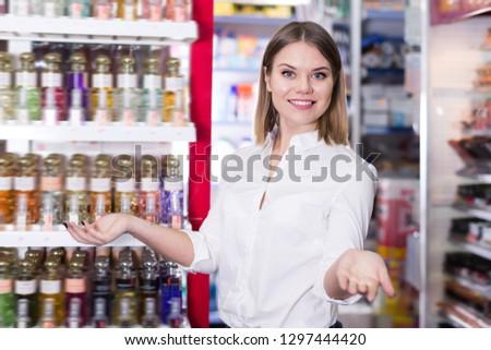 Happy salesgirl proposing stylish fragrances of perfume in cosmetic shop #1297444420