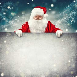 Happy Santa Claus holding blank advertisement banner background with copy space. Smiling Santa Claus pointing in white blank sign. Christmas theme, sales