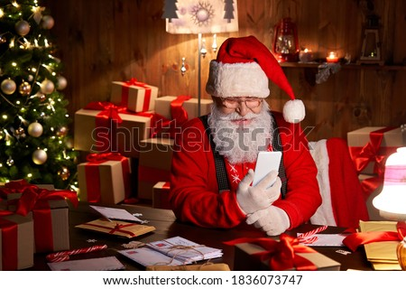 Happy Santa Claus holding smartphone holding cell phone using mobile app for social distance communication, watching videos or video calling in virtual online chat sit at home table late on xmas eve.
