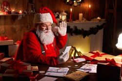 Happy Santa Claus holding smartphone video calling kid talking to child in virtual video online chat meeting sit at home table late with presents on xmas eve. Merry Christmas social distance concept.