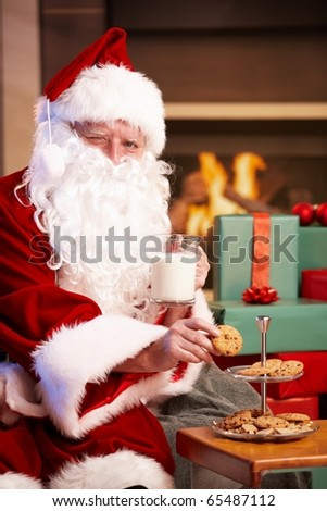 Happy Santa Claus sitting at fireplace drinking milk eating chocolate chip cookies, looking at camera, winking?