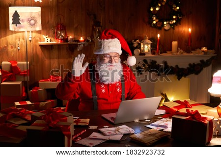 Happy Santa Claus waving hand video calling kid talking to child greeting on Merry Christmas, Happy New Year in virtual video online chat on laptop sitting at home table late with present on xmas eve.