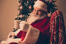 Happy Santa Claus wearing red costume holding cup of hot drink