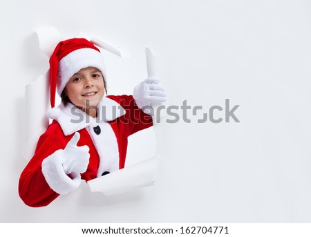Happy santa costume boy leaning through paper hole - giving thumbs up sign, with copy space
