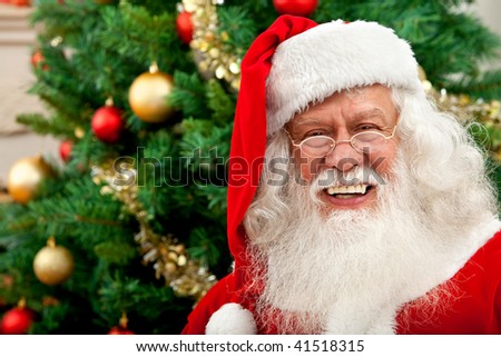Happy santa portrait with a Christmas tree behind indoors