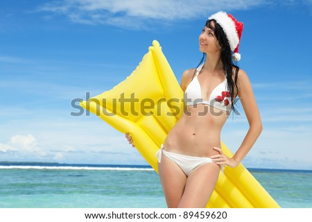 Happy santa woman with inflatable mattress on the beach. Christmas vacation