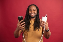 Happy satisfied African American guy with dreadlocks standing isolated on red wall, holding mobile phone connected to power bank through USB cable, charging his device, smiling and looking at camera