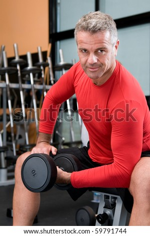 Happy satisfied mature man lifting weights at gym