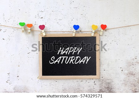 Happy Saturday - Concept words on the blackboard hanging with rope on rustic wooden background