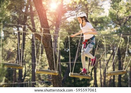 Happy school girl enjoying activity in a climbing adventure park on a summer day - Shutterstock ID 595597061