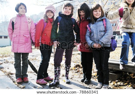 happy school girls running outdoor at sunny autumn day