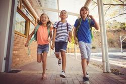 Happy school kids running in corridor at school