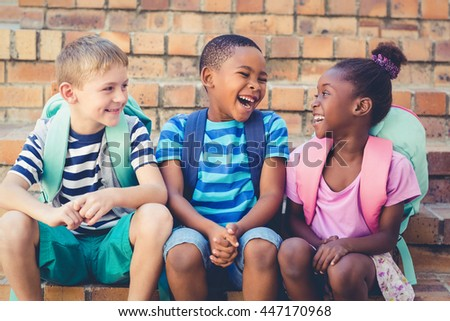 Happy school kids sitting together on staircase at school