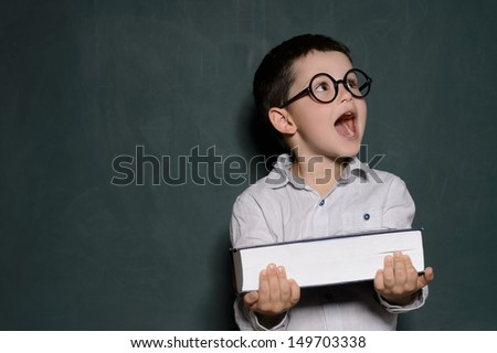 Happy schoolboy. Cheerful little schoolboy in glasses holding a book and laughing while standing in front of blackboard