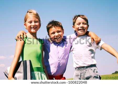 Happy schoolboy embracing his friends outdoor